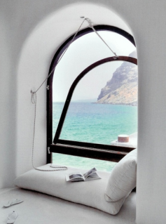 white cushions  and books near arched window looking over Mediterranean