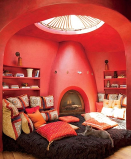 red adobe fire place with large shag ottoman and library